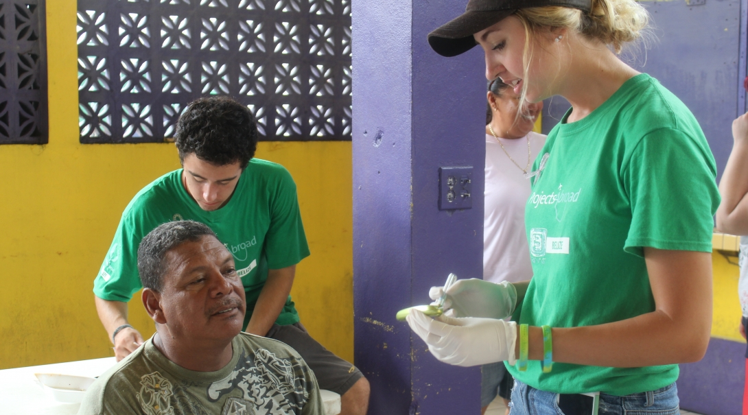 Interns take blood sugar measures as part of their public health work in Belize with a group.